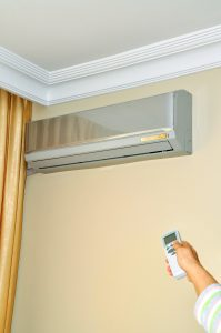 ductless-unit-on-wall-hand-with-remote
